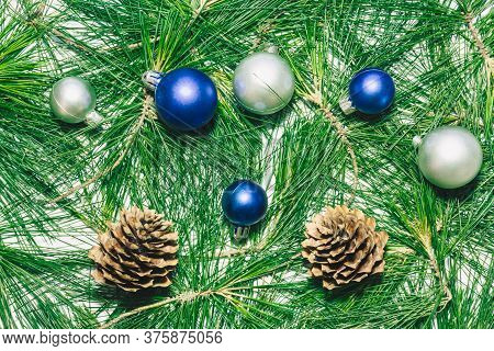 X-mas Background With Christmas Balls, Pinecones And Green Pine Leaves.