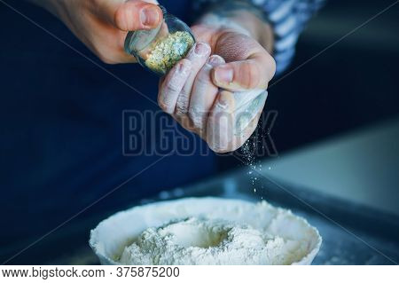 A Cook In A Blue Apron Holds A Glass Salt Shaker In His Flour-stained Hands, And Pours The Seasoning