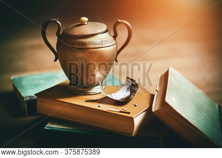 An Old Elegant Vase With An Ornament That Grants Wishes Stands On Old Battered Books, And Next To It