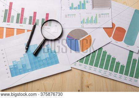 Magnifying Glass And Documents With Analytics Data Lying On Wood Table