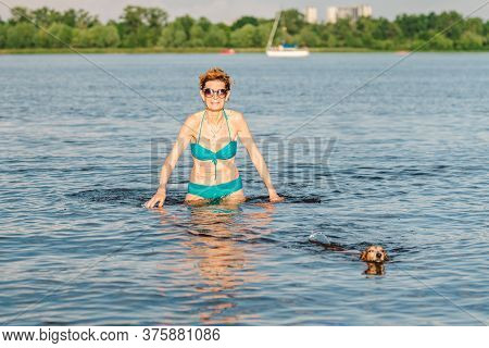 A Mature Caucasian Woman Teaches Swimming A Dachshund Dog. An Adult Woman In Sunglasses Spends Time