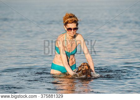 Mature Caucasian Woman Helps Her Little Old Dachshund Dog To Swim In Water. Spend Summer Time With A