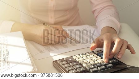 Financial Data Analyzing. Close-up Photo Of A Businesswoman Hand Writing And Counting On Calculator