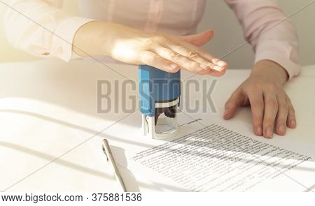 Young Businesswoman Or Notary Public Sitting At The Desk In Office And Stamping Document Contract