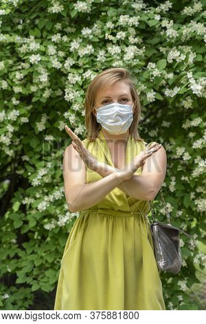 A Woman In A Green Dress And A Medical Mask Crossed Her Arms In A Prohibitory Sign Near A Flowering
