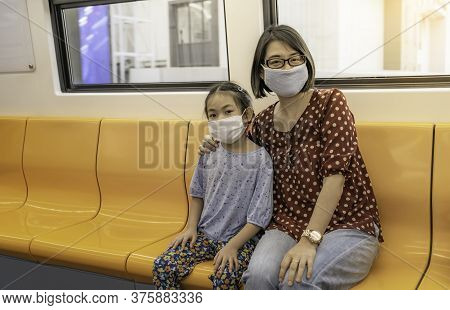 Portrait Of Asian Or Thai Mother And Little Daughter Sitting On Sky Train Of Bangkok, Thailand. Moth