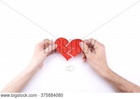 Female And Male Hands Hold A Broken Heart On A White Background With Wedding Rings. Marriage Problem