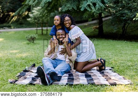 Family Picnic In The Park. Happy African Family With Child Girl, Wearing Casual Stylish Clothes, Sit