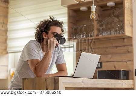 Male Freelancer Working Remotely From Home, Drinking Coffee And Using Laptop Computer; Web Developer