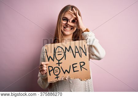 Young beautiful redhead woman asking for women rights holding banner over pink background with happy face smiling doing ok sign with hand on eye looking through fingers