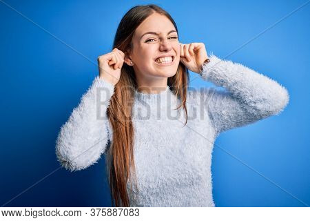 Young beautiful redhead woman wearing casual sweater over isolated blue background Smiling pulling ears with fingers, funny gesture. Audition problem