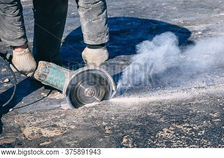 Circular Saw Cutting Reinforced Concrete Slab During Roof Repair. Worker Hands With With Electric An