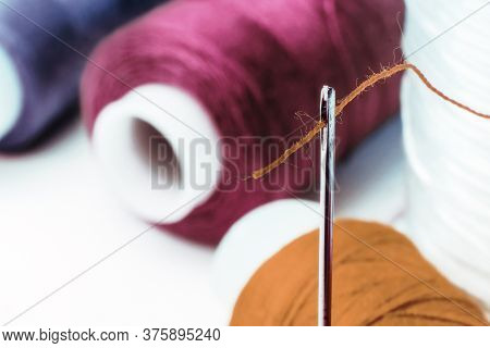 Multi-colored Sewing Threads. Spools Of Thread. Needle With Thread In The Eye Of The Needle.