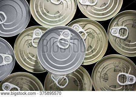 Flat Bottom Filled With Cans Of Golden Tuna And A Tin On A Silver Plate.