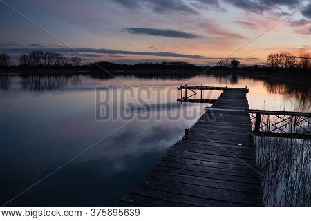 Wooden Jetty On A Quiet Lake, Evening Colored Clouds By Sunset