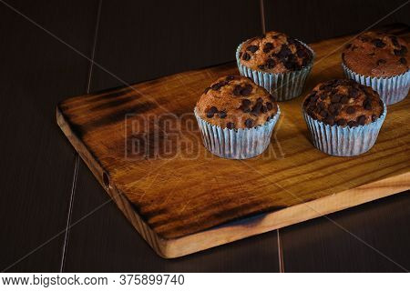 Exquisite Chocolate Muffins And Chocolate Chips Fresh From The Oven On Top Of Burned Pine Wood And U
