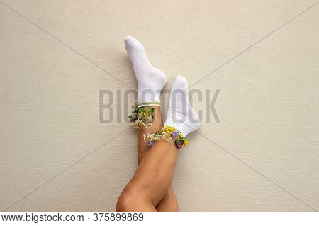 Upside Down View Of Female Legs With Fresh Flowers In Socks. Hipster Girl With Flowers From White So