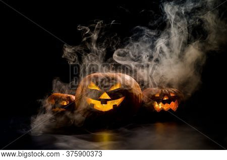 Three Creepy Halloween Steaming Pumpkins With A Carved Luminous Smirk On A Black Background. A Handm