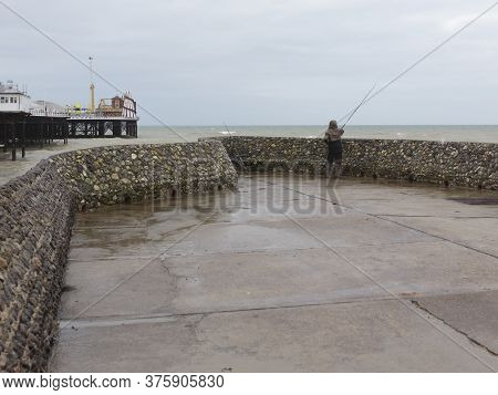 A Man Fishing Off Of A Groyne By Brighton Palace Pier In Stormy Weather, Brighton, England