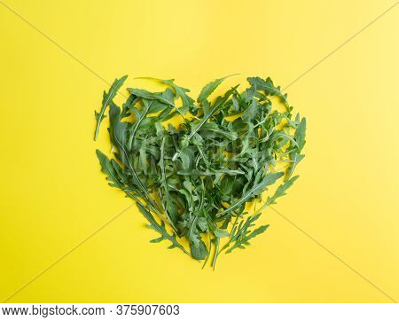 Heart Shape Arugula On Yellow Background. Minimal Concept Of Picture For Harvesting Market Sale