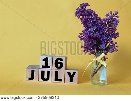 July 16.july 16 On Wooden Cubes On A Yellow Background.vase With Lilac .photos For The Holiday .