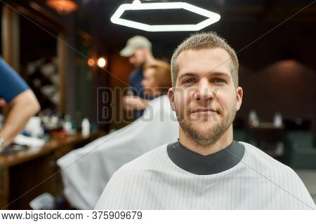 Getting New Haircut. Portrait Of Young Handsome Bearded Man Sitting In Barbershop Chair And Smiling