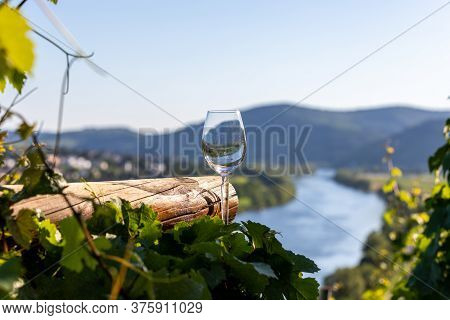 Empty Wine Glass Next To Wooden Beam And Valley Of River Moselle In Background