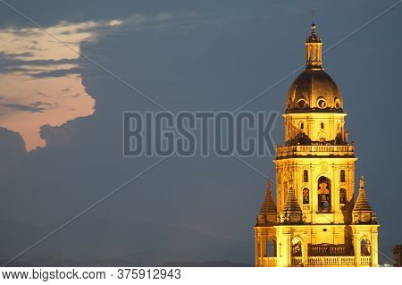 Illuminated Tower Of The Cathedral Of Murcia Stands Out Over The City Buildings