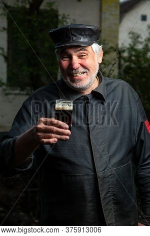 Cheerful Elderly Man With Black Old-fashioned Old Clothes And A Leather Cap With A Glass Of Beer In