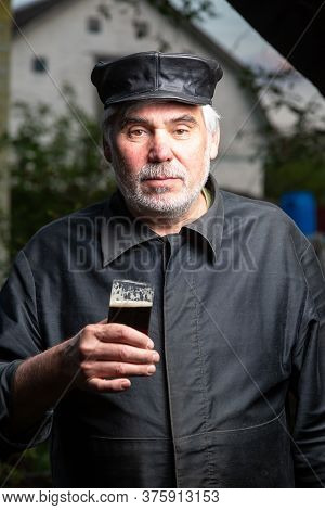 Serious Kind Elderly Man With Black Old-fashioned Old Clothes And A Leather Cap With A Glass Of Beer