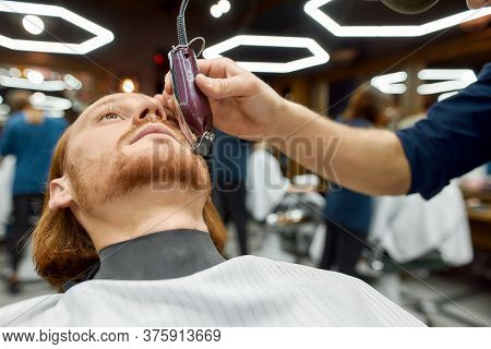 Beard Correction. Close Up Of A Young Handsome Redhead Guy Sitting In Barbershop Chair And Getting B