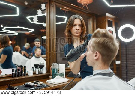 Visiting Beauty Salon. Young Guy Sitting In Barbershop Chair While Professional Focused Barber Girl