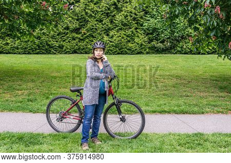 Pregnant Woman In A Park With Bicycle Talking On The Phone.