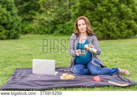 Pregnant Woman Pouring Coffee Otr Tea From Stainless Thermos In The Park After Working On A Computer