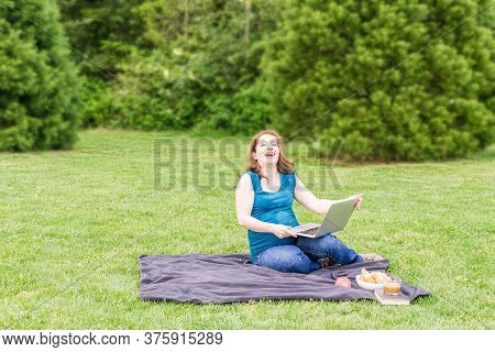 Beautiful Pregnant Woman Is Laughing In A Summer Green Park With Laptop And Bicycle.