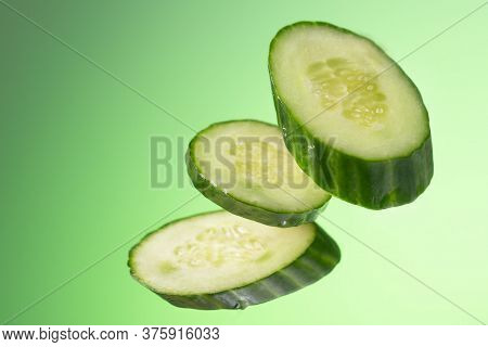 Three Pieces Of Cucumber Hang Arbitrarily On A Green Background With A Gradient.