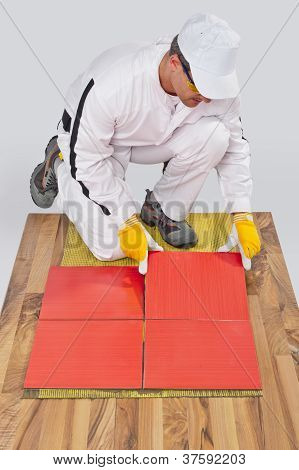 Worker Applies Ceramic Tiles On Wooden Floor With Fiber Mesh