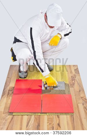 Worker Applies Ceramic Tiles On Wooden Floor With Notched Trowel