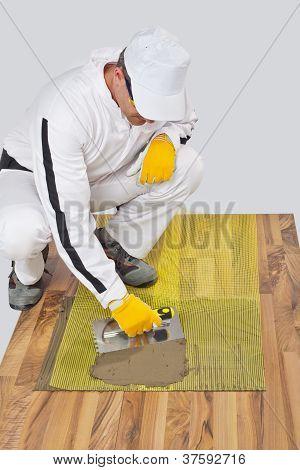 Worker Applies Tile Adhesive With Reinforcement Mesh On Wooden Floor