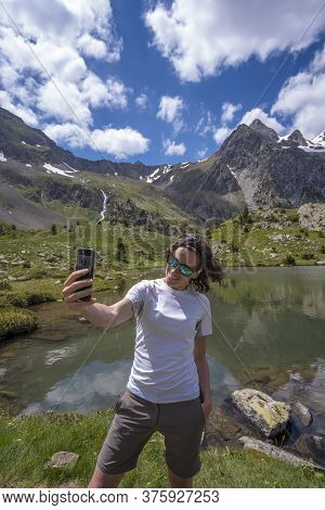 Woman Taking A Selfie With A Smartphone On A Glacial Lake Vertical