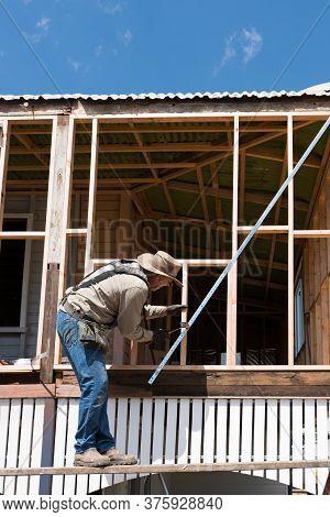 Carpenter Working On Old Timber Framed High Set Queenslander Style House