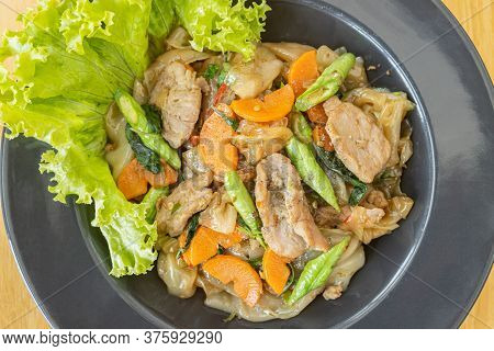 Stir Fried Noodle And Pork And Carrot And Yardlong Beans And Lettuce With Black Soy Sauce On Top Vie