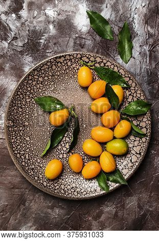 Fresh Kumquat With Leaves On A Plate, Brown Background, Top View