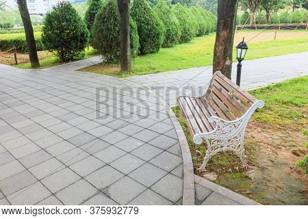 View of green garden with a small square and wooden bench for resing in the corner of the city park,Fuzhou,Fujian,China