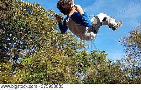 Boy Child Swinging On Swing At Playground
