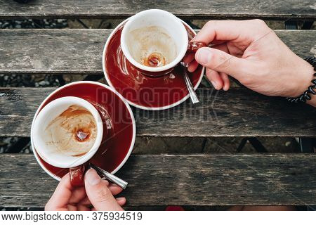 Close Up Of Human Hands Touching Empty Couple Cup Of Coffee On The Wooden Table. Remains Of Coffee S
