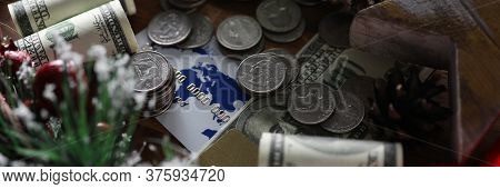 Close-up Of Coins Banknotes And Credit Cards. Christmas Presents And Savings. Pinecones And Sprig Wi