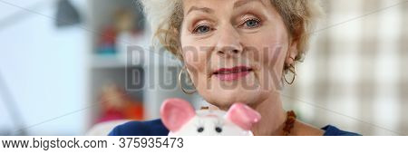 Happy Elderly Woman Shows Pink Ceramic Piggy Bank. Initial Savings Fund. Expenses Include Food. Succ