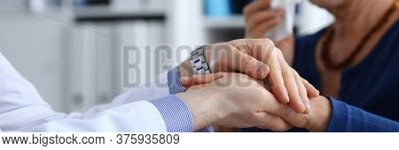 Focus On Male Hands Of Doctor Holding Arms Of Sick Elderly Woman. Therapist Supporting And Calming I