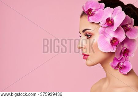 Portrait Of Beautiful Young Woman With Orchid. Brunette Woman With Luxury Makeup. Perfect Skin. Eyel